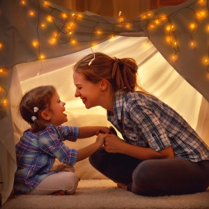 woman and girl playing in tent with fairy lights