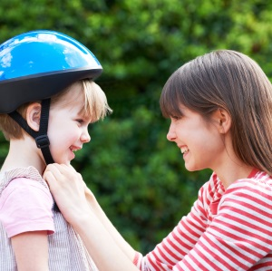 child putting on bike helmet