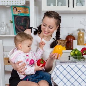 woman in kitchen with little girl and vegetables